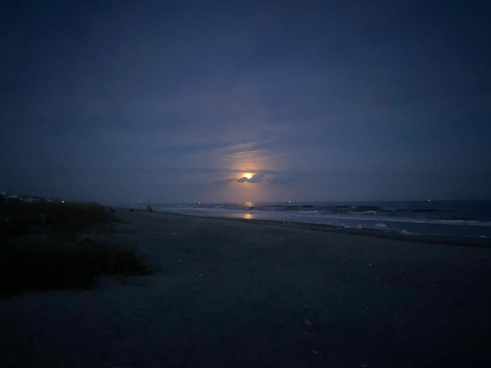A dimly lit beach with the waves rolling in. A full moon peaks out from behind some clouds.