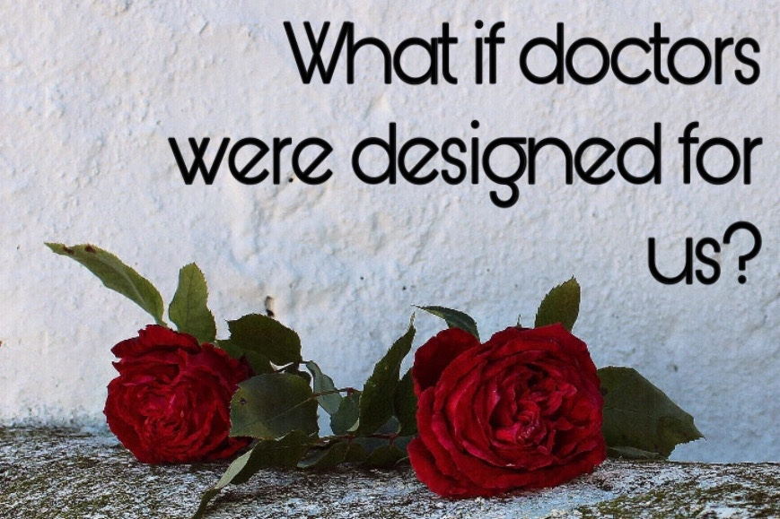 "Two roses layed on the concrete floor, text above against wall says ""what if doctors were designed for us?"""