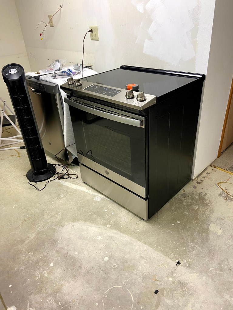 Stainless steel electric stove with front controls installed where door once was, and a new dishwasher sitting next to it.