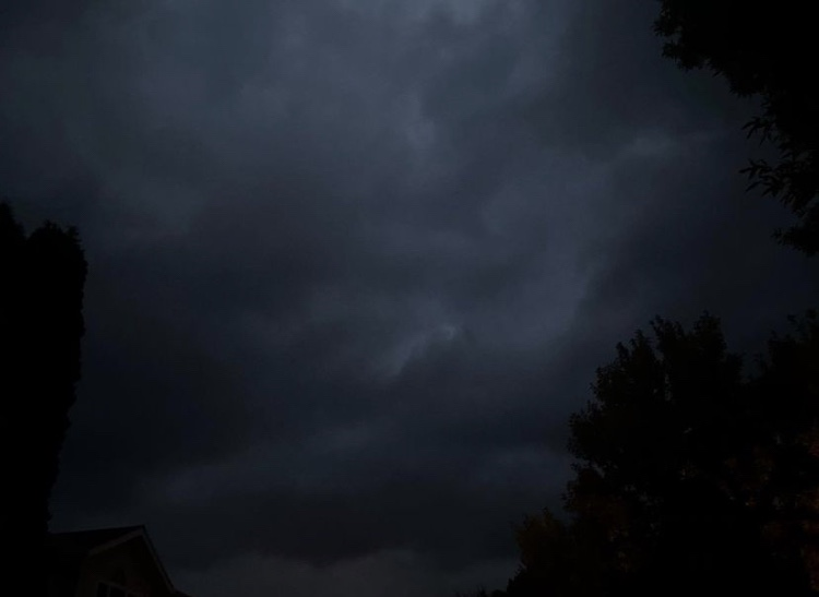Dark nighttime sky, tree silhouettes bordering the frame with ominous dark storm clouds rolling in
