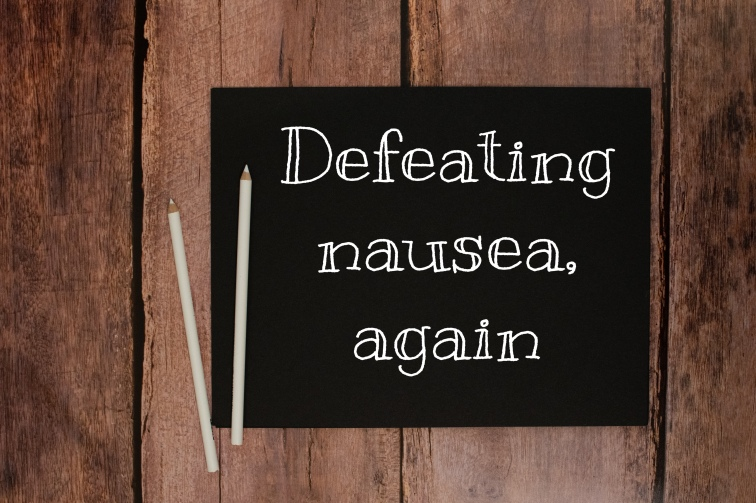 "Wooden background with a black paper that says ""defeating nausea again"""