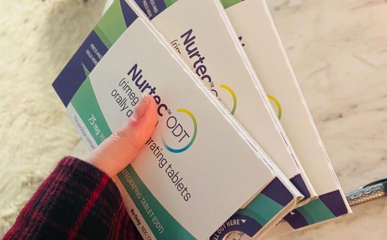 Hand holding three packets of Nurtec prescriptions
