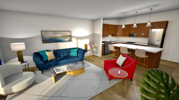 Standing in the corner where the office is, you turn and see the whole living space with the kitchen behind it. The deep navy couch has teal and gold pillows tossed across it and looks striking across from the pink chair.