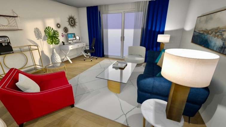 Walking along the back of the pink chair to another corner of the room, you look across the living room. A deep navy couch is to your right. You can see directly into the small office space from this angle.