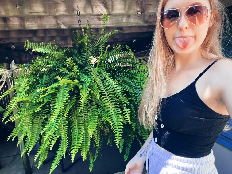 Picture of me, long blond hair is straight I'm sticking my tongue out as I pose with a large Boston fern