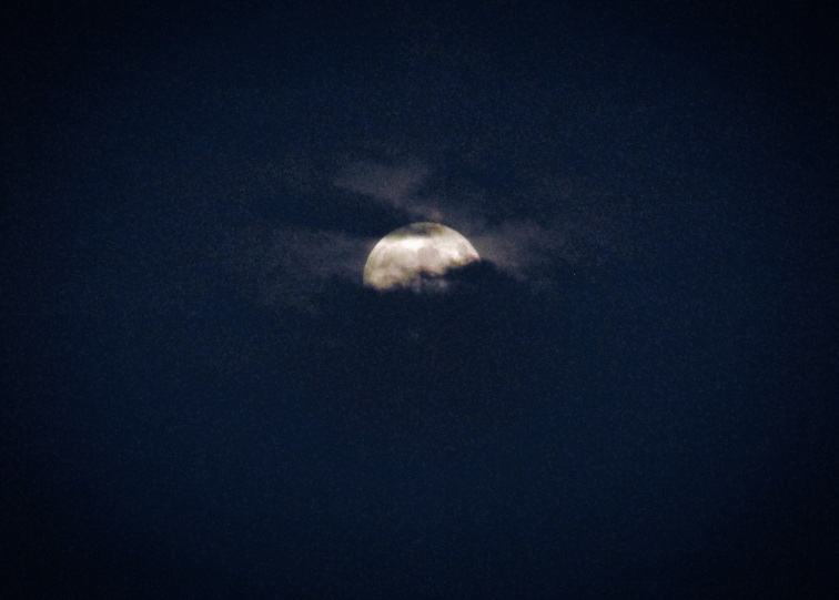 Full moon rising through thick clouds